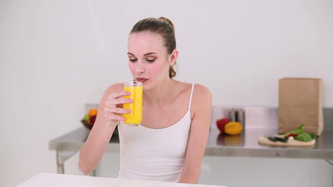 Smiling model drinking glass of orange juice Footage