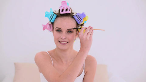 Young model in hair rollers brushing her eyebrows Footage