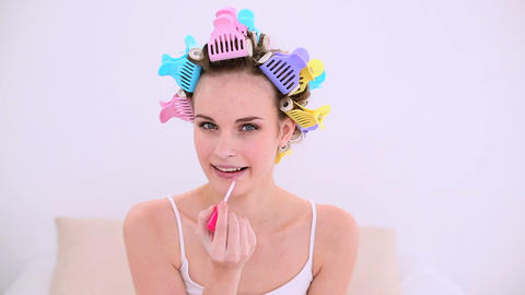 Young model in hair rollers putting on lip gloss Footage