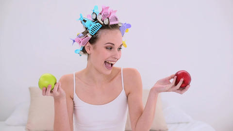 Young model in hair rollers holding red and green  Footage