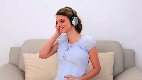 Pregnant woman listening to music on the couch Footage
