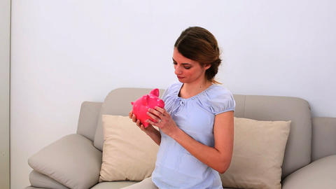 Pregnant woman holding a piggy bank on the sofa Footage