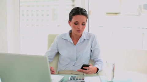 Pretty businesswoman texting on her smartphone Footage