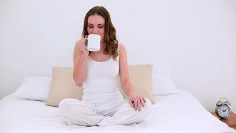 Pretty model sitting on bed drinking mug of coffee Footage