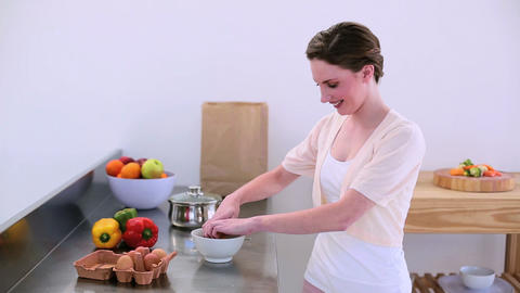 Pretty model standing in kitchen preparing an omel Footage