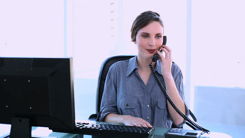Pretty businesswoman answering phone Footage