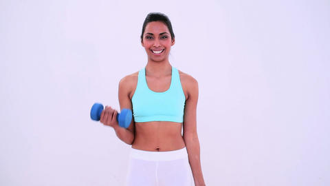 Fit woman lifting hand weights and smiling at came Footage