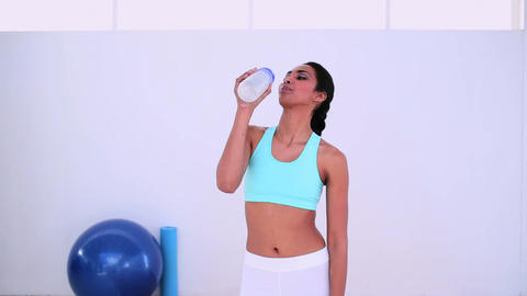 Fit woman walking and drinking from sports bottle Footage