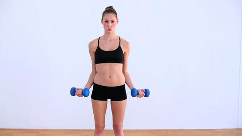 Pleased woman exercising with dumbbells Footage