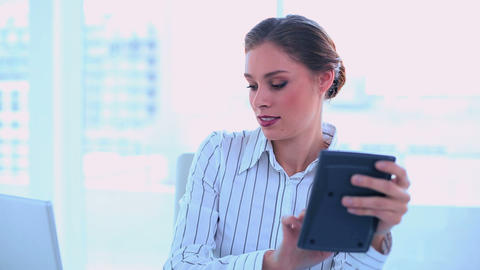 Concentrated businesswoman using a calculator Footage