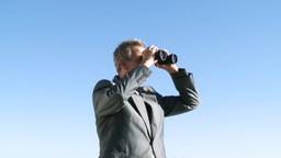 Businessman watching through a binoculas Footage