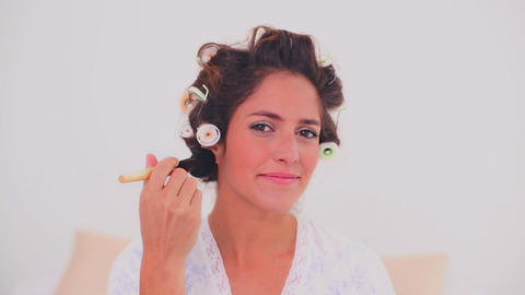 Content woman in hair curlers applying powder Footage