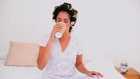 Cheerful woman in hair curlers enjoying coffee Footage