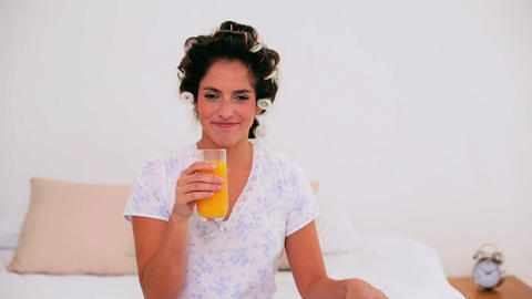 Joyful woman in hair curlers enjoying orange juice Footage