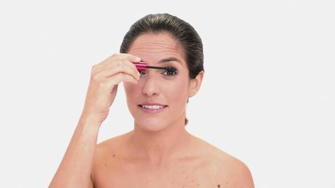 Thoughtful brunette woman applying mascara Footage