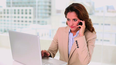 Gorgeous brunette businesswoman using a laptop whi Footage