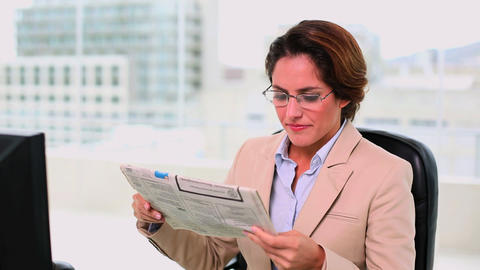 Concentrated attractive businesswoman reading a ne Footage