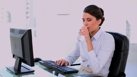 Calm beautiful businesswoman drinking water while  Footage