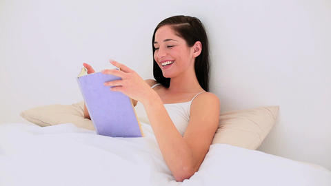 Attractive brunette reading a book in bed Footage