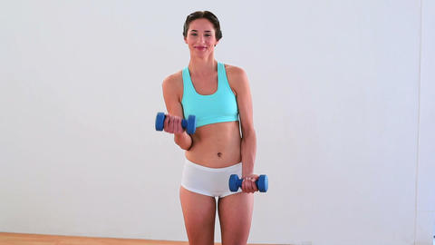 Fit brunette lifting dumbbells and smiling Footage