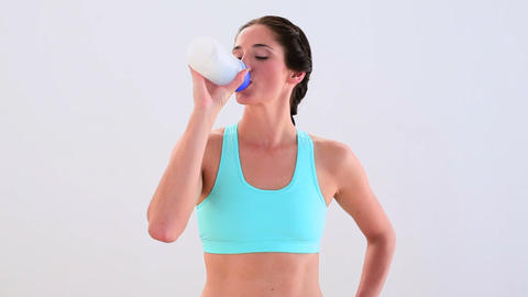 Fit brunette drinking from sports bottle and smili Footage