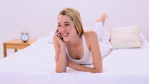 Laughing gorgeous blonde lying on bed phoning Footage