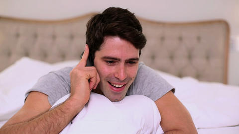 Smiling handsome man phoning in bed Footage