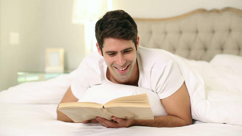 Smiling handsome man reading in bed Footage