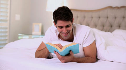 Happy handsome man reading in bed Footage