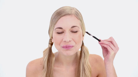 Happy nude blonde using eyebrow brush Footage