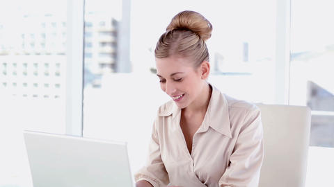 Happy blonde businesswoman using laptop Footage