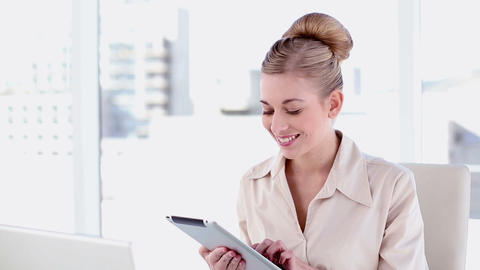 Happy blonde businesswoman using tablet Footage