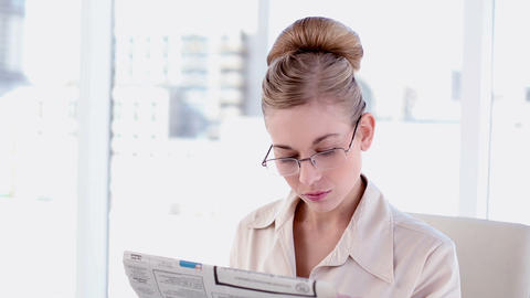 Content blonde businesswoman reading newspaper Footage