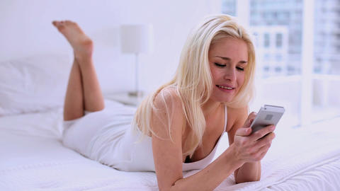 Pretty young woman text messaging with her smartph Footage