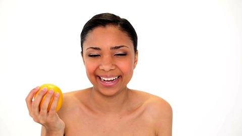 Cute laughing woman holding orange Footage