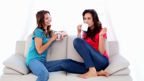 Lovely chatting women sitting on couch holding mug Footage