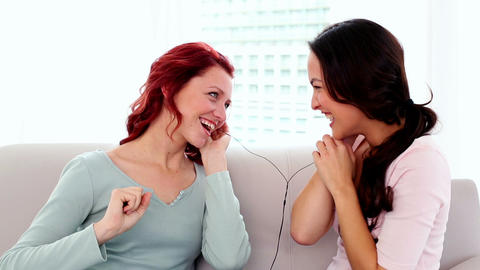 Amused gorgeous women listening with headphones to Footage