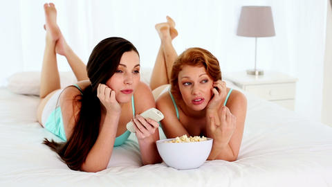 Attractive bored women watching television lying o Footage