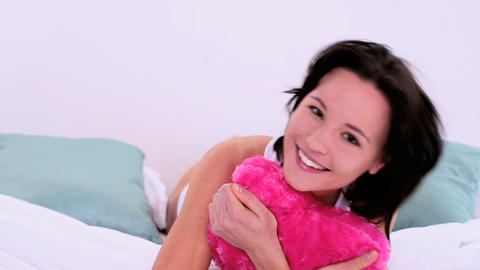 Lovely cheerful woman cuddling with heart pillow Stock Video Footage