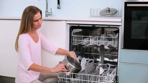 Annoyed woman filling the dish washer Footage
