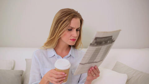 Calm blonde woman reading newspaper sitting on cou Footage