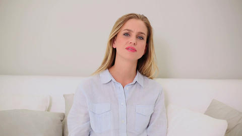 Blonde woman watching television sitting on couch Footage