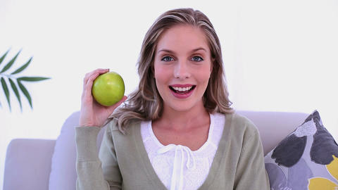 Cheerful lovely woman showing a green apple Footage