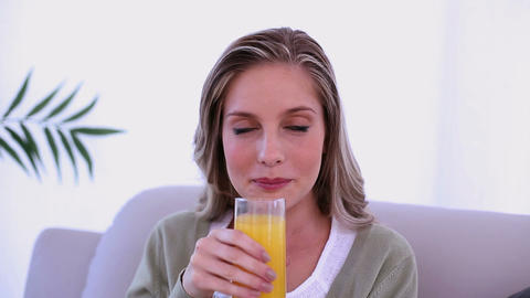 Beautiful blonde woman drinking a glass of orange  Footage