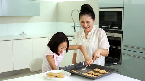 Mother and daughter taking cookies from baking tra Footage