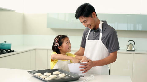 Father and daughter making cookies together Footage