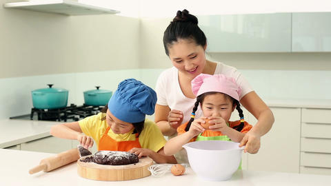 Smiling mother and cute daughters baking together Footage