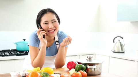Happy woman preparing dinner and talking on the ph Footage