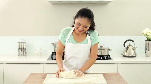 Smiling woman kneading dough Footage