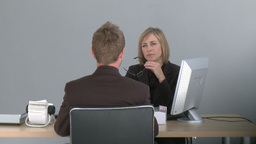Two associates talking at a desk Footage